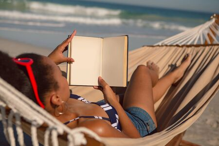 Rear view of African american woman reading a book while relaxing on hammock on beach in the sunshine