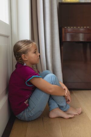Side view of sad Caucasian girl sitting alone in corner at home Stock Photo