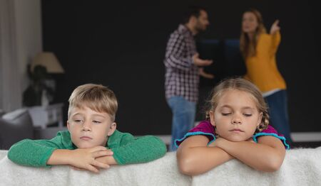 Front view of sad kids leaning on sofa while Caucasian parents arguing in background in a comfortable home Stock Photo
