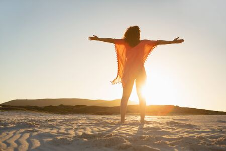 Low angle view of mixed race woman with arms stretched out standing on beach in the sunshine Stock Photo