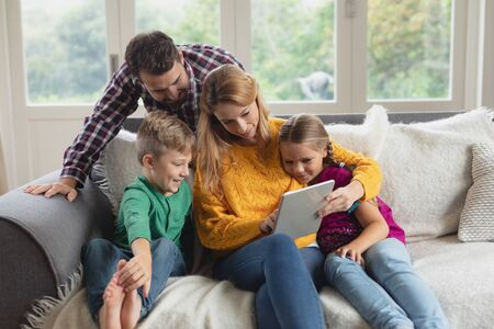 Front view of Caucasian family using digital tablet on the sofa in a comfortable home