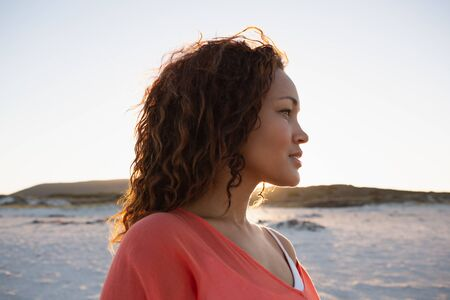 Side view of beautiful mixed race woman looking away on the beach Stock fotó