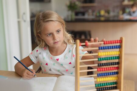 Front view of Caucasian girl doing homework at table in a comfortable home Stock Photo