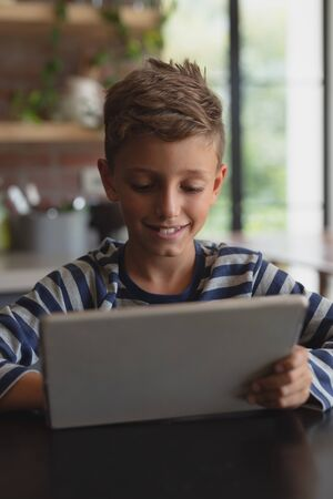 Front view of happy Caucasian boy using digital tablet at table in kitchen at home