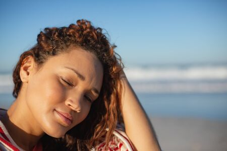 Portrait of beautiful mixed race woman with eyes closed wrapped in blanket sitting on beach in the sunshine