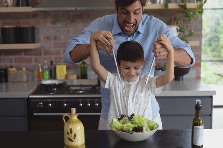Front view of Caucasian father and son preparing vegetable salad in kitchen at home Reklamní fotografie