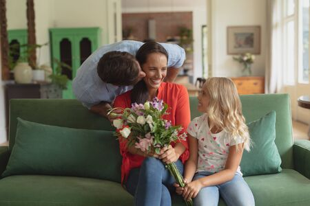Front view of Caucasian daughter giving bouquet to mother while father kissing her in living room at home Stock Photo
