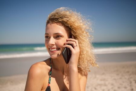 Side view of beautiful Caucasian woman talking on mobile phone on the beach Stock Photo