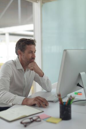 Front view of thoughtful Caucasian business male executive working on computer at desk in a modern office