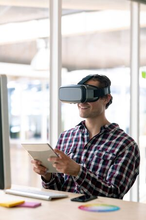 Side view of Caucasian male graphic designer using virtual reality headset while working on digital tablet at desk in office Stock Photo - 124672840