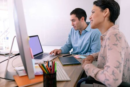 Side view of diverse graphic designers working together at desk in a modern office Stock Photo - 124672844