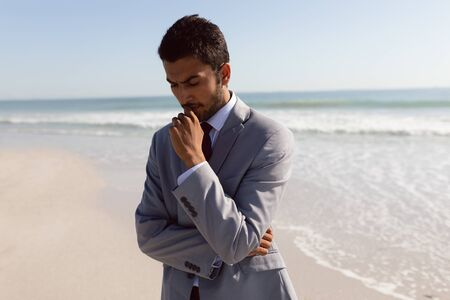 Front view of thoughtful young Mixed-race Businessman standing on the beach Banco de Imagens