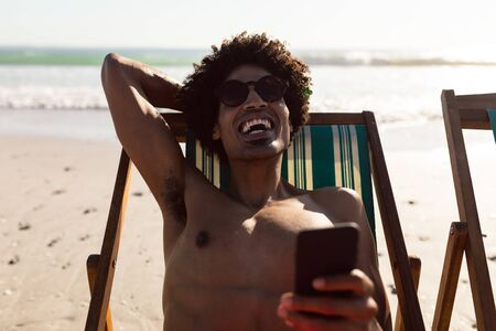 Front view of happy African-american man using mobile phone while relaxing in a beach chair on the beach