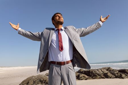 Front view of young Mixed-race Businessman standing with arms outstretched and eyes closed on the beach