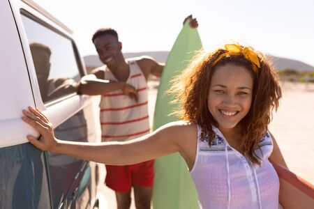 Front view of happy young Mixed-race couple with surfboard leaning on camper van at beach 版權商用圖片