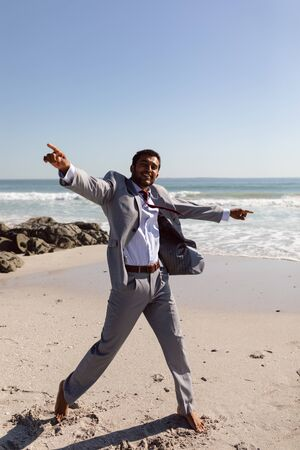 Portrait of happy young Mixed-race Businessman dancing on the beach