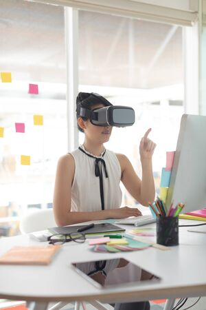 Side view of beautiful Asian female graphic designer using virtual reality headset at desk in a modern office