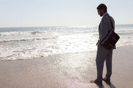 Rear view of thoughtful young Mixed-race Businessman standing on the beach Stock Photo