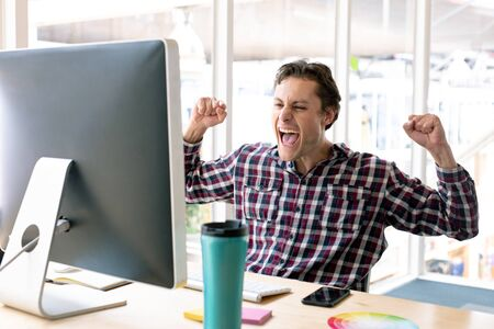 Side view of happy Caucasian male graphic designer celebrating success at desk in a modern office