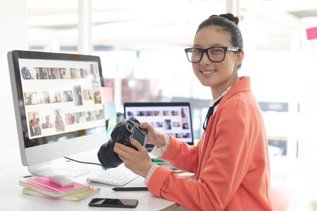 Front view of Asian female graphic designer looking at camera while working at desk in a modern office Stock Photo