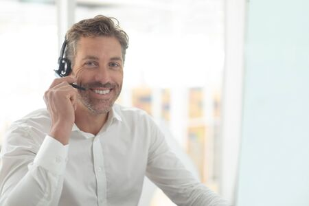 Vista frontale del dirigente del servizio clienti maschio caucasico che parla con le cuffie alla scrivania in un ufficio moderno