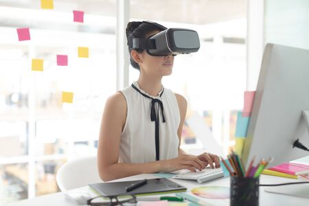 Side view of Asian female graphic designer using virtual reality headset while working on computer at desk in a modern office Stok Fotoğraf