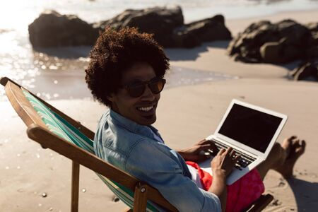 Rear view of young African-american man using laptop while relaxing in a beach chair on the beach