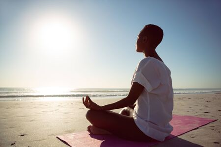 Side view of African-american woman performing yoga on the beach Stok Fotoğraf