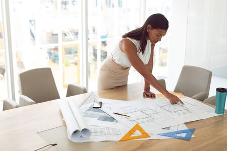 Side view of beautiful mixed race female architecture working on blueprint on table in a modern office Stok Fotoğraf
