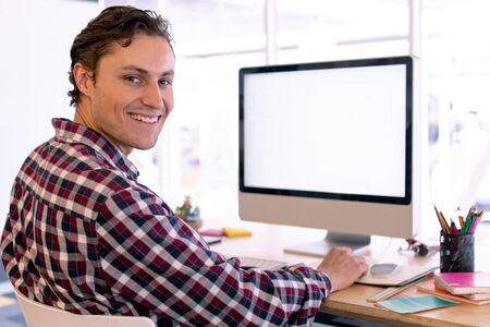 Side view of happy Caucasian male graphic designer looking at camera while working on computer at desk in a modern office