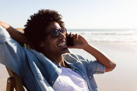 Front view of happy African-american man talking on mobile phone while relaxing in a beach chair on the beach