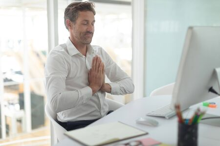 Front view of Caucasian business male executive doing yoga at desk in a modern office Stok Fotoğraf