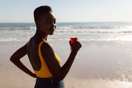 Portrait of African-american woman with cocktail drink standing on the beach Stok Fotoğraf
