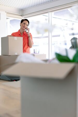 Front view of beautiful Caucasian businesswoman with cardboard boxes talking on mobile phone in new office