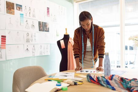 Front view of beautiful mixed race female fashion designer looking at sketches on table in a modern office Stok Fotoğraf