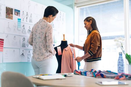 Rear view of diverse female fashion designers working together working on garment on dressmaker model in office Stock Photo