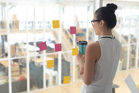 Rear view of thoughtful Asian female business executive holding water bottle and looking through window in a modern office Stok Fotoğraf