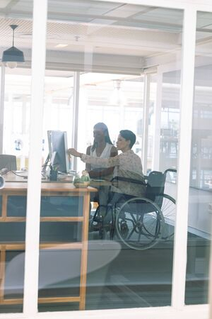 Side view of diverse female graphic designers discussing on computer at desk in a modern office. Disabled mixed-race female designer is sitting in wheelchair.