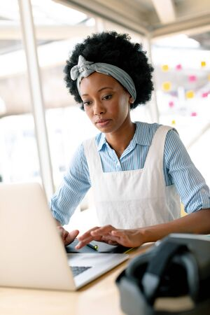 Side view of African american female graphic designer working on laptop at desk in office