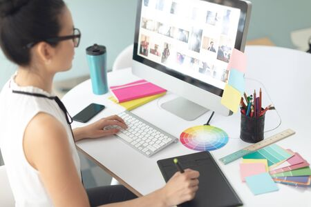 Rear view of attentive Asian female graphic designer using graphic tablet at desk in a modern office Imagens