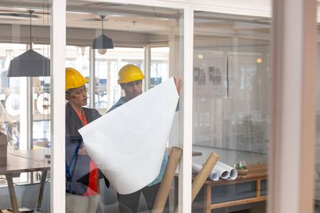 Front view of Caucasian architects discussing over blueprint in a modern office