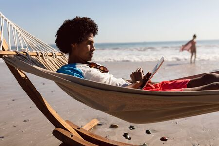 Side view of young African-american man using digital tablet while relaxing in a hammock on the beach Stok Fotoğraf