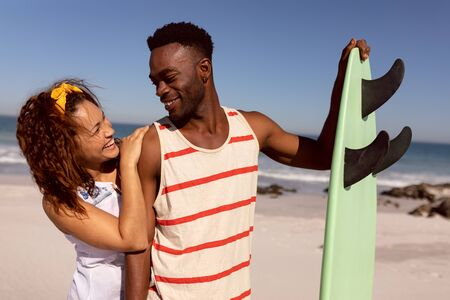 Front view of happy young Mixed-race couple with surfboard looking each other on beach in the sunshine