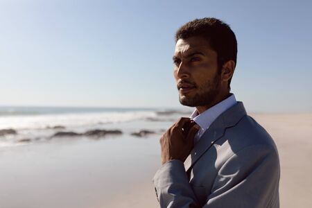 Front view of thoughtful young Mixed-race Businessman adjusting his tie on the beach Banco de Imagens