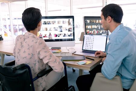 Rear view of diverse graphic designers working together at desk in a modern office. Disabled mixed-race female designer is sitting in wheelchair. Stock Photo