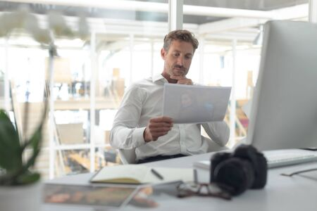 Front view of thoughtful Caucasian male graphic designer looking at photograph on desk in a modern office Stok Fotoğraf
