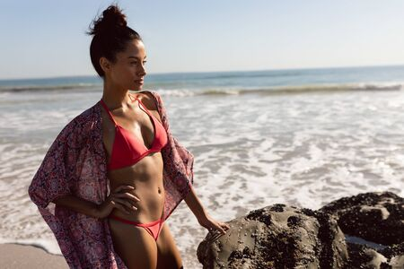 Side view of thoughtful Mixed-race woman in bikini standing on the beach