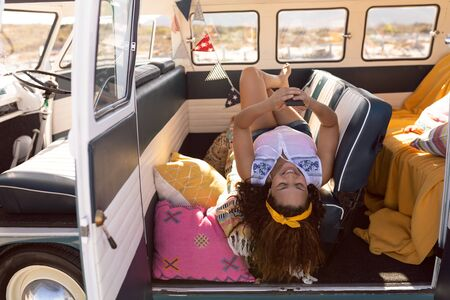 Side view of happy young Mixed-race woman using mobile phone in camper van at beach