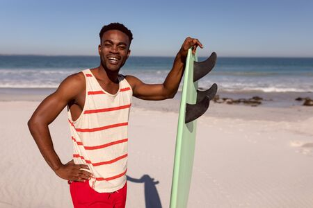Front view of happy young African-american  man standing with surfboard on beach in the sunshine