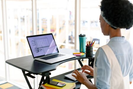 Side view of African american female graphic designer working on laptop at desk in office Stock Photo - 124673152